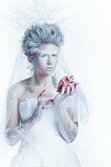 Snow queen with an unusual makeup and heart in hands