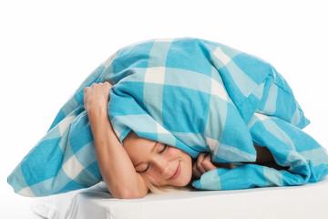 Frau liegt unter der Bettdecke und schläft