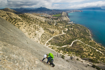 rock climber climbs mountain with sea on background
