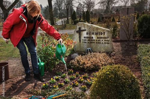 Foto op Plexiglas Begraafplaats Planting flowers on a grave in spring