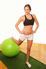 Young woman exercising with gym ball