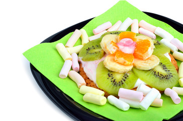 Fruit dessert with exotic fruits and marshmallow on black plate