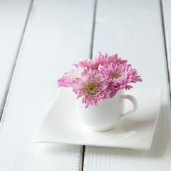 Cup full of pink  mum flowers on  old wooden table.