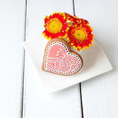 Cup full of gerbera  flowers and  heart shape cookie on whi
