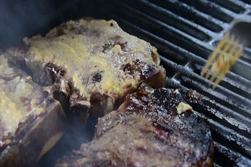 flipping garlic encrusted steaks sizzling on the grill