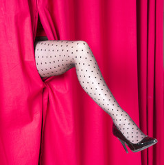 Womans leg wearing black tights appearing through a red curtain