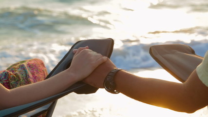 Loving Couple Holding Hands While Sitting On Outdoor Chairs At