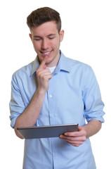 Mann im blauen Hemd grübelt am Tablet Computer