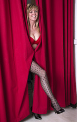 Woman in underwear  appearing through red curtain