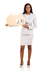 african american businesswoman holding paper house
