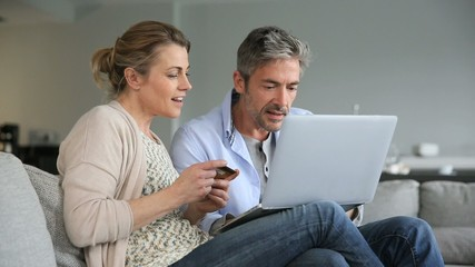 Couple shopping online with credit card at home