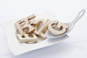 Buchtstabensuppe, Holzbuchstaben und Porzellanlöffel Teller