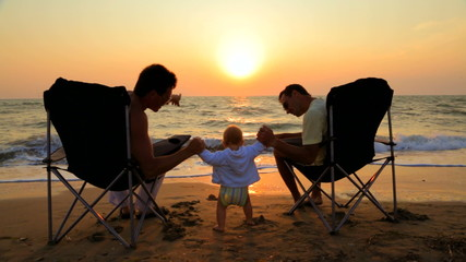 Two Men In Outdoor Chairs And Baby On The Beach At Sunset