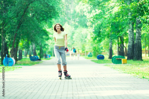 Roller skating sporty girl in park rollerblading on inline skate - 80810354