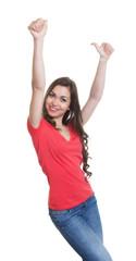 Jubelnde Frau mit langen dunklen Haaren und rotem Shirt