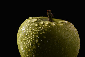 A wet green macro apple with water drops on black background