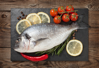 Fresh fish, lemon, spices and cherry tomatoes on a stone board