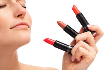 Beautiful woman is holding differend lipsticks