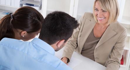 Junges Paar bei einer Besprechung in der Bank oder Versicherung