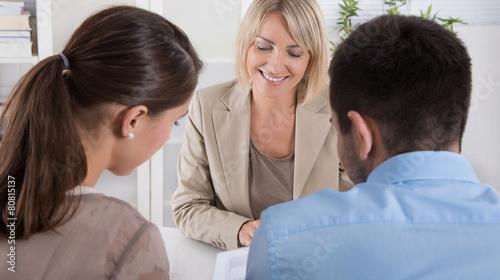 Kunden und Berater im Gespräch - sitzend an einem Tisch - 80815137