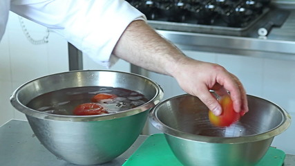 Chef cooking minced tomatoes in boiling water in a pot. Restaura