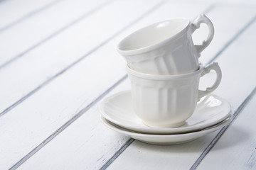 Two white cups on a white wooden table. Vintage.