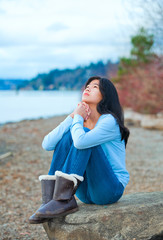 Teen girl sitting on boulder along lake shore praying