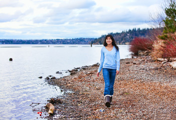 Young teen girl walking along rocky shoreline of lake in early s