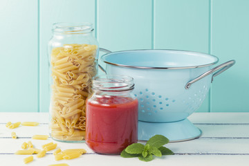 The ingredients to cook macaroni: pasta, tomato and a strainer