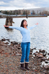 Young teen girl with arms lifted and outstretched, praising God