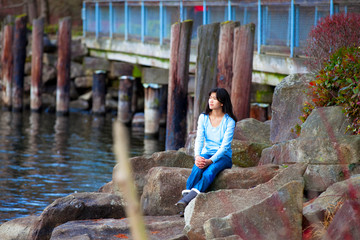 Young teen girl sitting on large boulders along lake shore, look