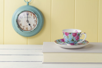 A tea cup, a book, a turquoise clock, a yellow wainscot. Vintage