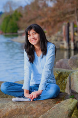 Young teen girl relaxing on large boulder along lake shore, smil