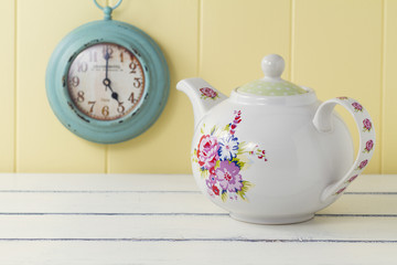 A teapot on a white wooden table and a turquoise clock. Vintage