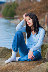 Young unhappy teen girl sitting on rocks along lake shore, looki