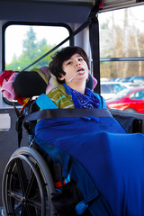 Disabled eight year old boy in wheelchair buckled on school bus