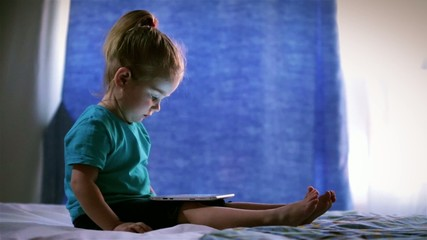 Little cute baby girl sitting on bed uses a Tablet PC, touches