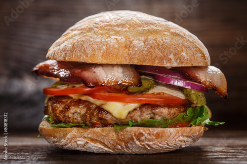 Poster Kruidenierswinkel Delicious burger on wooden board