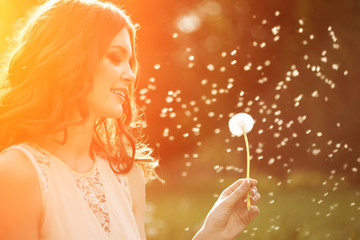 Young spring fashion woman blowing dandelion in spring garden. S
