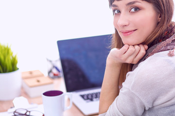 Portrait of  woman sitting at  desk with a laptop