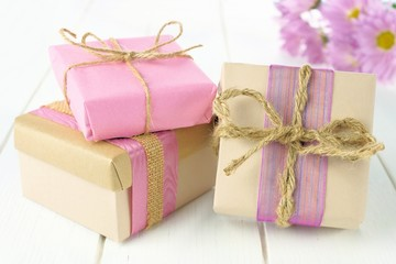 Gift boxes with brown and pink paper wrap on white wood