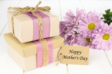 Gift boxes with Mother's Day tag on white wood with flowers