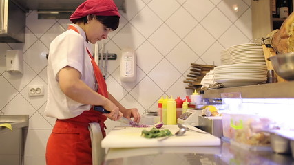 Woman chef sliced fresh vegetables and dill