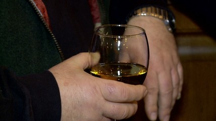 Hand of men with a glass of cognac.