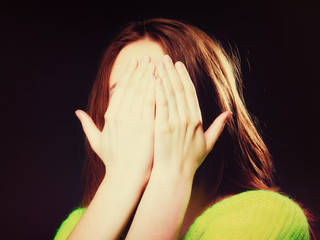 teen girl covering her face with hands on black