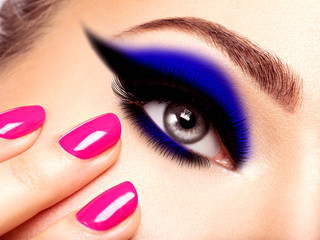female eye with blue and black make-up with pink nails