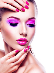 Face of a beautiful  woman with vivid eye make-up and  pink nail