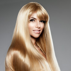 Beauty young woman with luxurious long blond hair. Haircut with