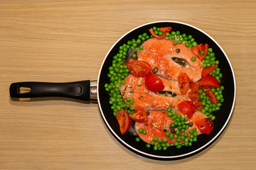 Pan full of salmon steacks, peas, tomatoes and capers