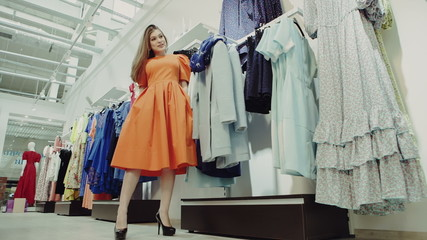 Woman shopping looking in mirror trying clothes dress in